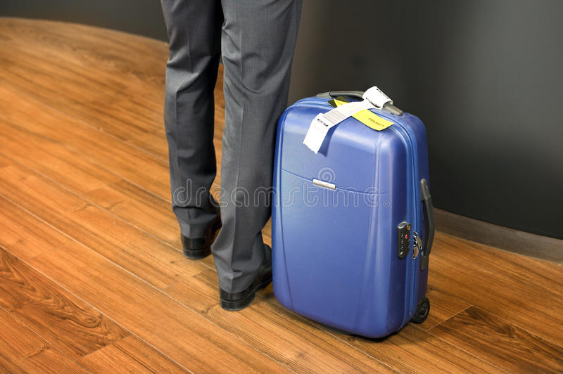 Business class passenger at airport check in. Business class passenger, with a carry on suitcase with priority luggage tags standing at an airport check-in stock photos