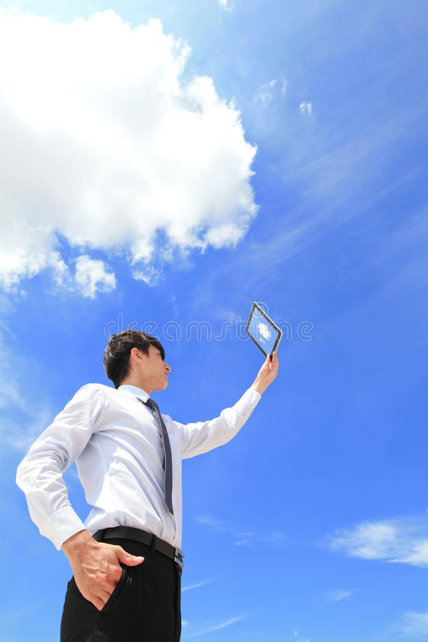 Business and cloud computing concept. Young business man using tablet pc and look to blue sky and cloud with cityscape in the background, business and cloud royalty free stock photos