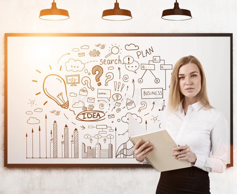 Business coach and business idea. Portrait of a blond businesswoman holding a notebook and standing near a whiteboard with a business idea sketch on it. Toned royalty free stock photography