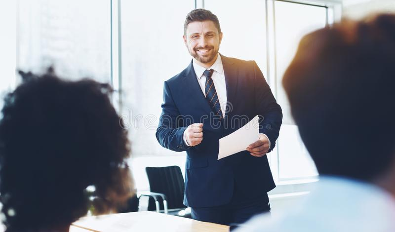 Business coach speaking to young people at training seminar stock images