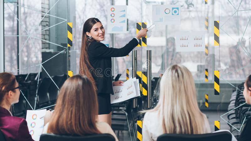 Business coaching advanced company training growth. Business coaching. Advanced company training. Smiling coach pointing at expected growth rates stock photos