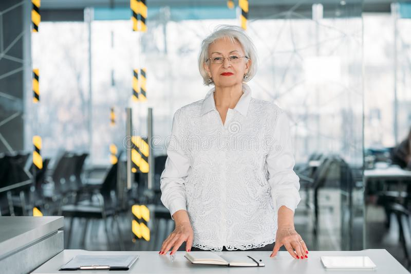 Business coaching senior female team leader. Business coaching. Senior female team leader. Successful business woman standing at conference hall, holding royalty free stock images