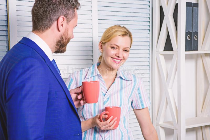 Business colleague having coffee break in the office. Two business people working together casual. Cheerful work of two. People during break time in bright stock photo