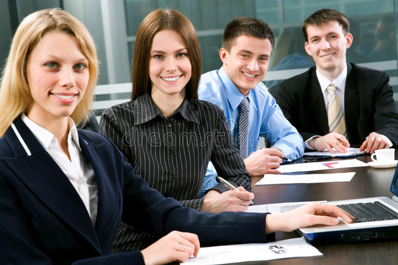 Business colleagues. Four business colleagues sitting around table and working together, looking at camera, smiling stock photo