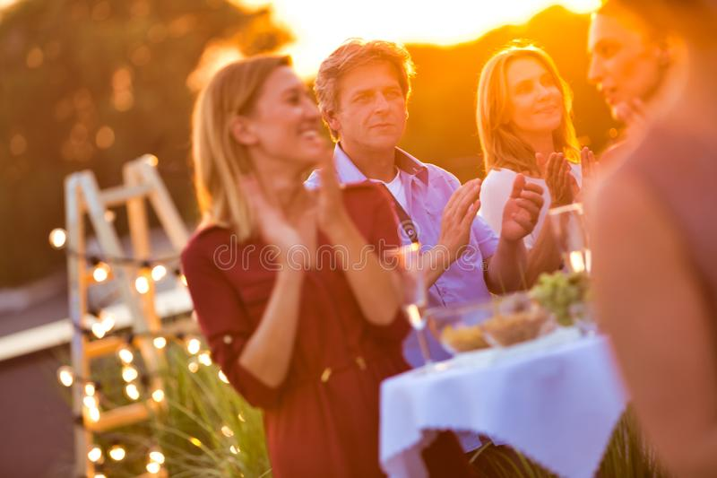 Business colleagues applauding during rooftop success party. With yellow lens flare in background stock photo