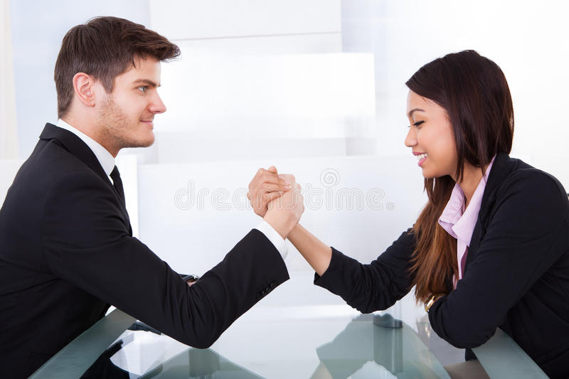 Business colleagues arm wrestling. Side view of business colleagues arm wrestling at desk in office stock photography
