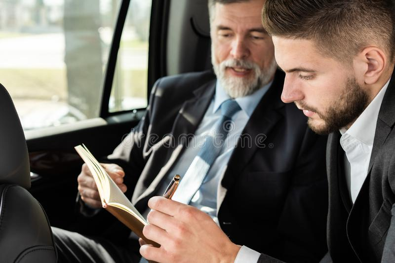 Business colleagues discussing business ideas while sitting in backseat of the car or taxi. stock photo