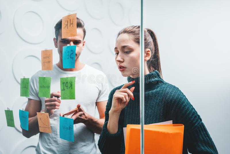 Business colleagues discussing new ideas and using sticky glass note wall stock photography