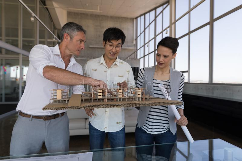 Business colleagues discussing over house model in office. Side view of standing mixed race business colleagues discussing over house model in modern office stock images