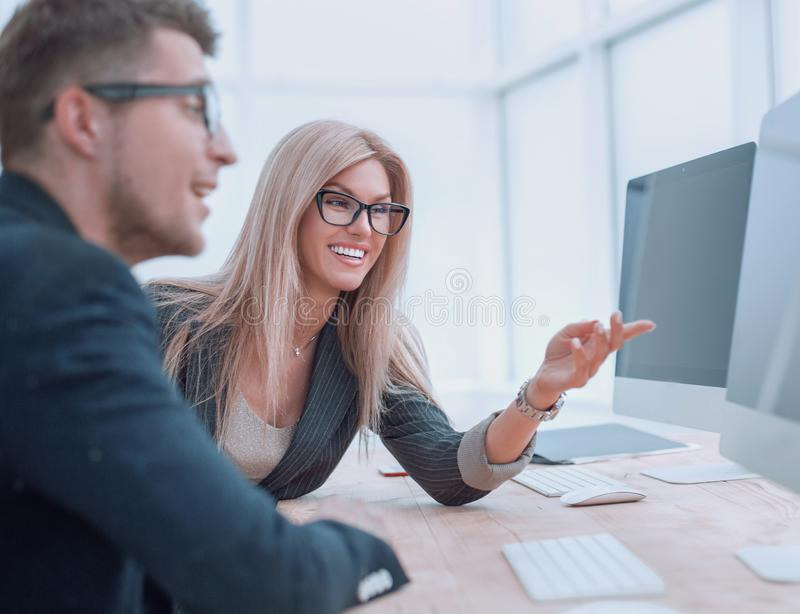 Business colleagues discussing work tasks sitting at a computer table royalty free stock image
