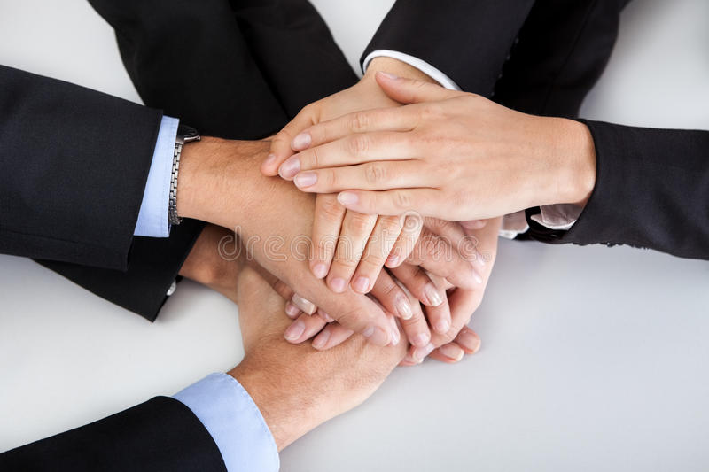 Business colleagues with hands stacked together stock photography