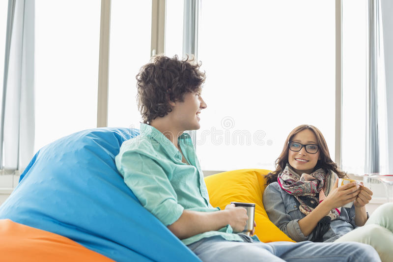 Business colleagues having coffee while relaxing on beanbag chairs in creative office royalty free stock photo
