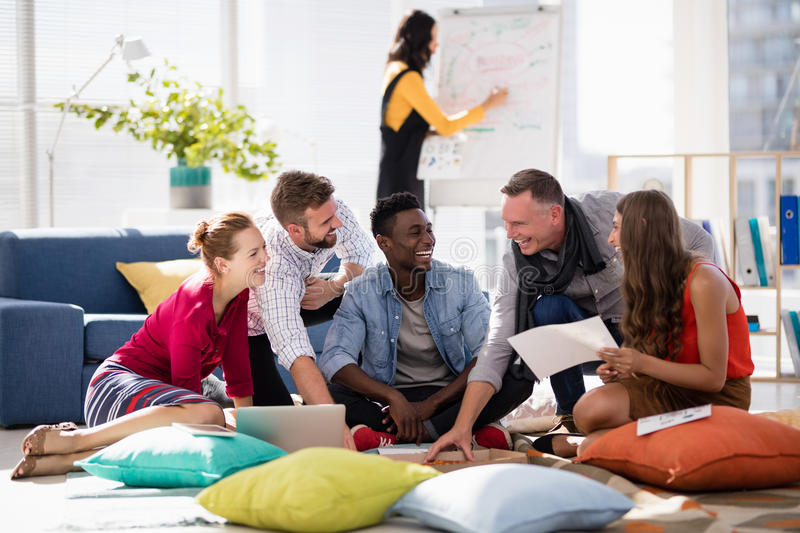 Business colleagues having pizza together while working in office. Team of business colleagues having pizza together while working in office stock photos