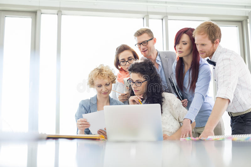 Business colleagues with laptop analyzing document in creative office royalty free stock image