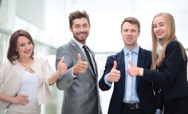 Business colleagues looking at camera and shoving thumbs up in t stock photo