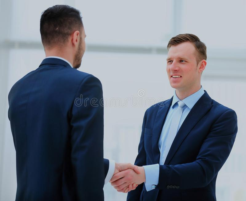 Business colleagues sitting at a table during a meeting with two male executives shaking hands. royalty free stock image