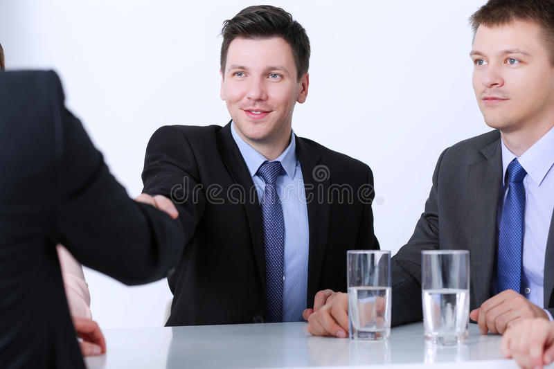 Business colleagues sitting at a table during a meeting with two male shaking hands stock photos