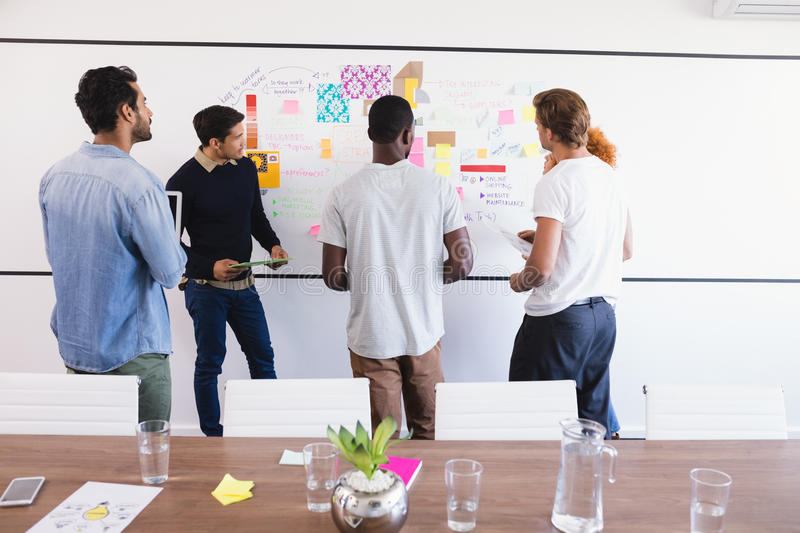 Business colleagues standing by whiteboard stock photography