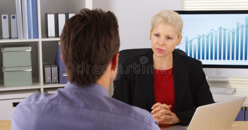 Business colleagues talking and listening in the office stock photography