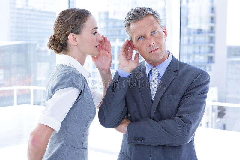 Business colleagues whispering stock photo