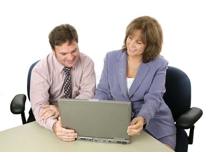 Business Colleagues at Work. A male and female business colleague working on a project together using a laptop. Or a professional showing something on the royalty free stock photography