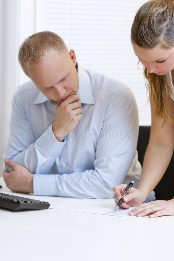 Business Colleagues Working. A businesswoman and a businessman planning and discuss. Pointing and looking at a printed diagram on a table stock photography