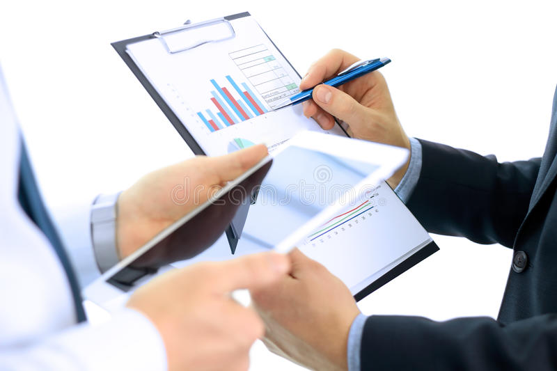 Business colleagues working and analyzing financial figures on a digital tablet.  stock photos