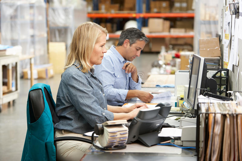 Business Colleagues Working At Desk In Warehouse. On Computer stock photography