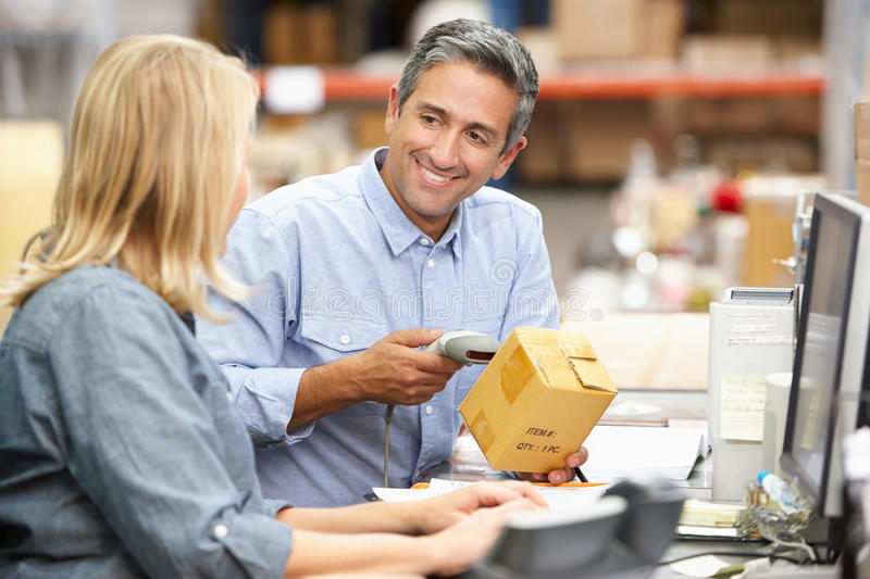 Business Colleagues Working At Desk In Warehouse. Smiling stock photos