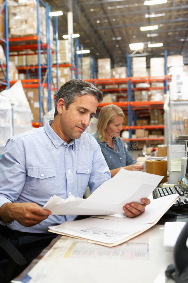 Business Colleagues Working At Desk In Warehouse. Looking At Notes royalty free stock photos