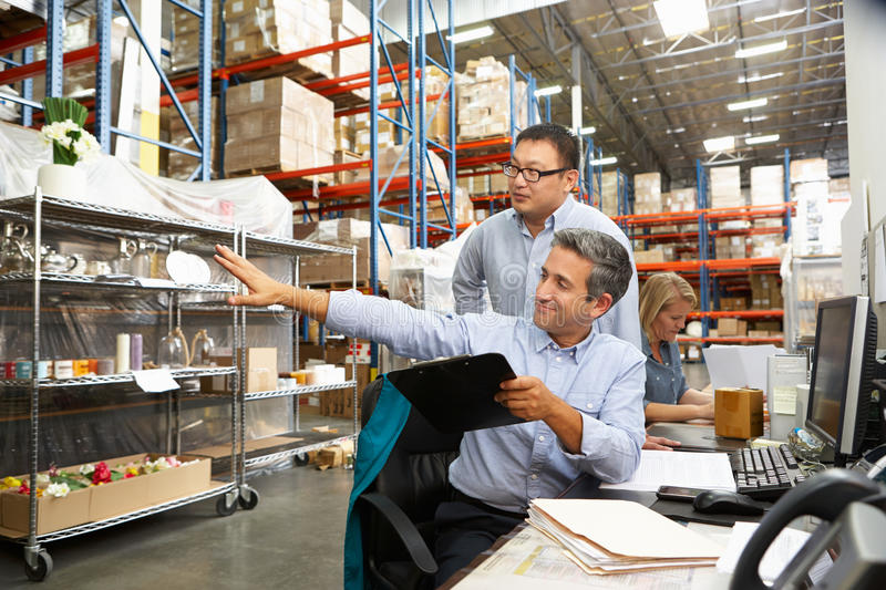 Business Colleagues Working At Desk In Warehouse. Talking stock images