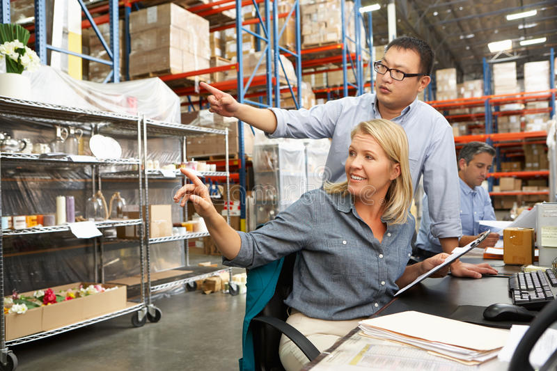 Business Colleagues Working At Desk In Warehouse. Smiling royalty free stock photography