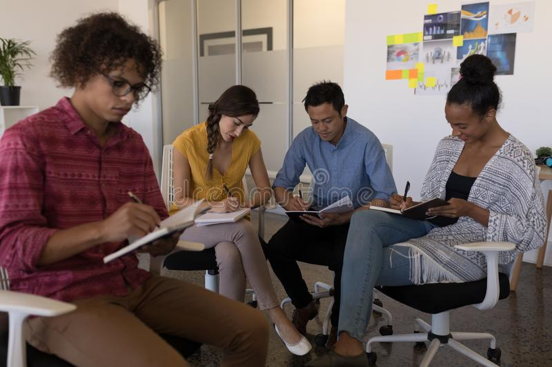 Business colleagues writing on a diary in office royalty free stock photography