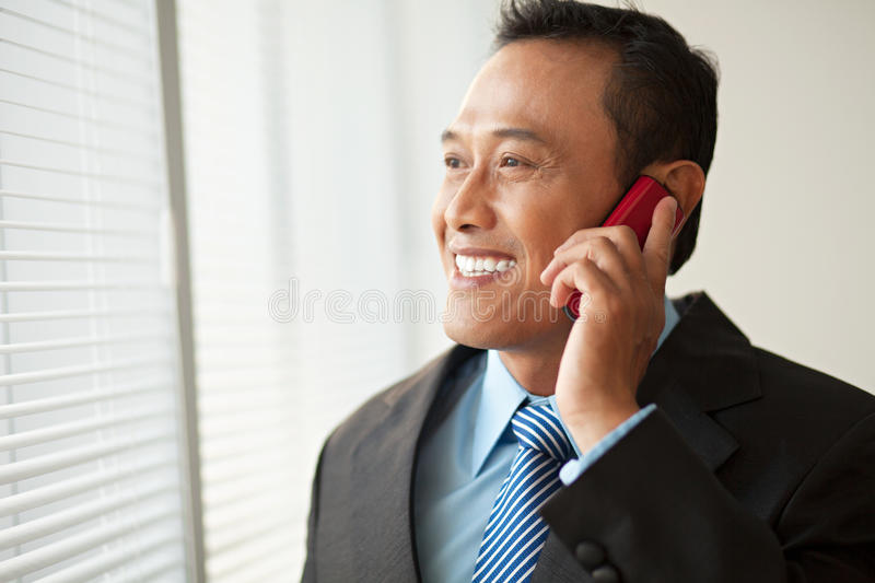 Business communication. Happy businessman talking on cell phone stock photo