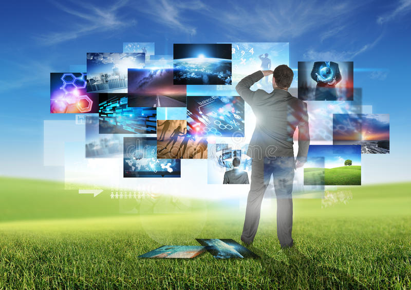 Business Communication. A businessman looking at floating media images stock images