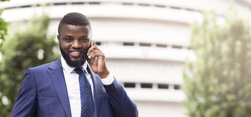 Business Communication. Cheerful Afro Businessman Having Phone Conversation Outdoors stock photo