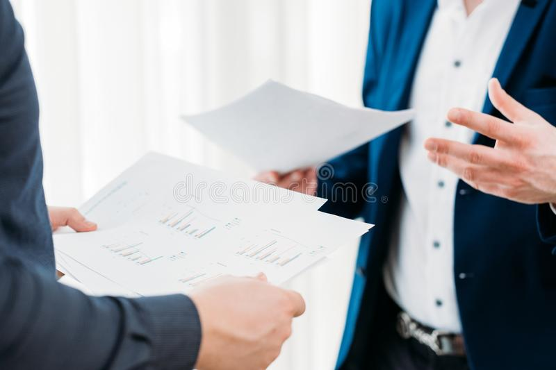 Business communication coworkers discuss documents. Business communication. coworkers exchange and discuss information. documents with statistics data reports royalty free stock images