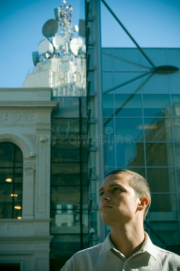 Business communications. A young business man standing in front of an office building with communication antennas in the background royalty free stock photography