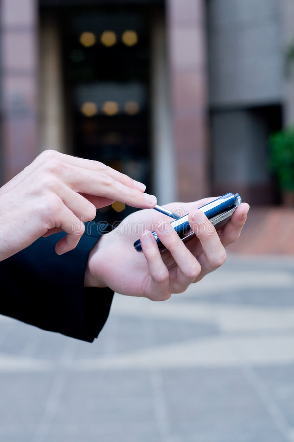 Business communications. A business man is using his palmtop (PDA) for business communications , background is a corporate building. focus on the PDA and front stock image