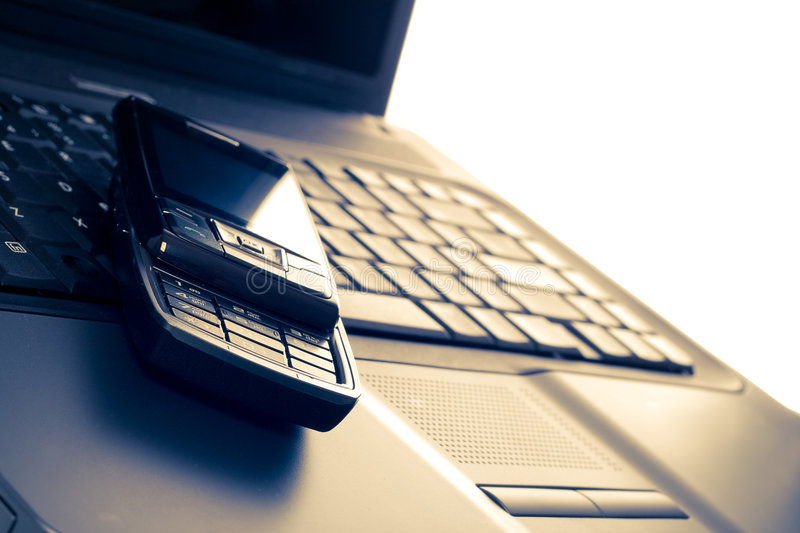 Business communications. Laptop and phone royalty free stock image