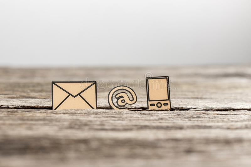 Business communications concept with three icons. For email, a web address and telephone on textured rustic wooden table stock image