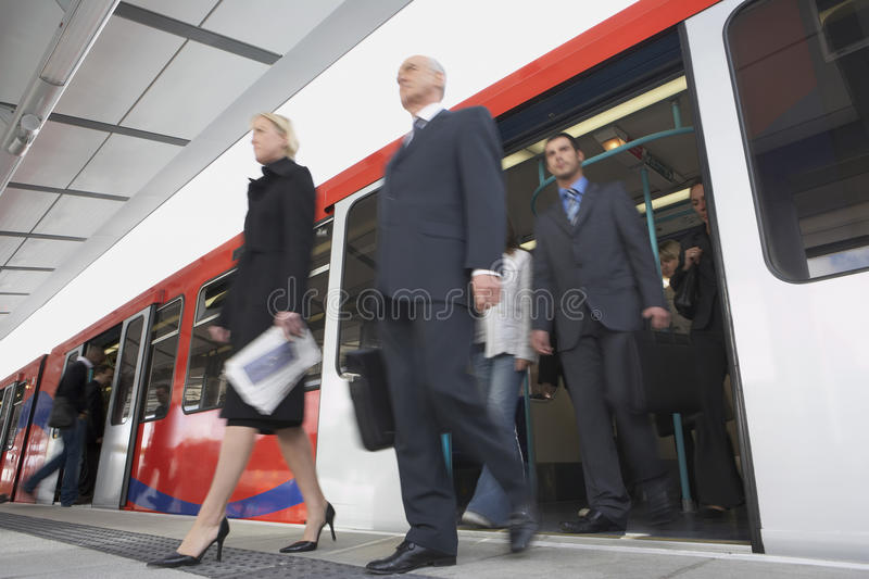 Business Commuters Getting Off Train. Low angle view of business commuters getting off a train stock images