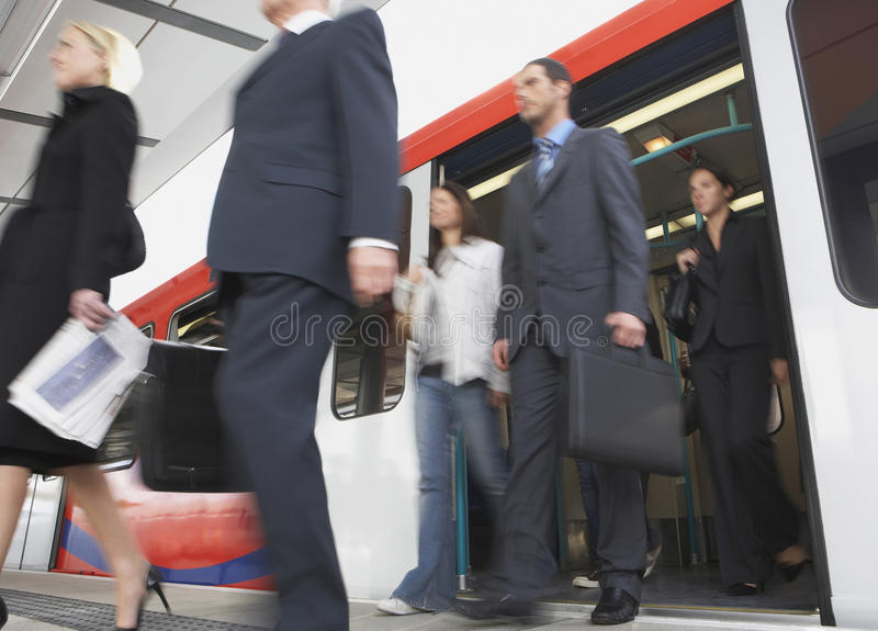 Business Commuters Getting Off Train. Low angle view of business commuters getting off a train royalty free stock images