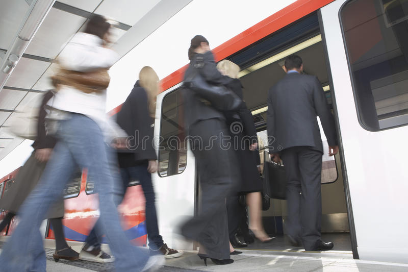 Business Commuters Getting Into Train. Low angle view of business commuters getting into a train royalty free stock photography
