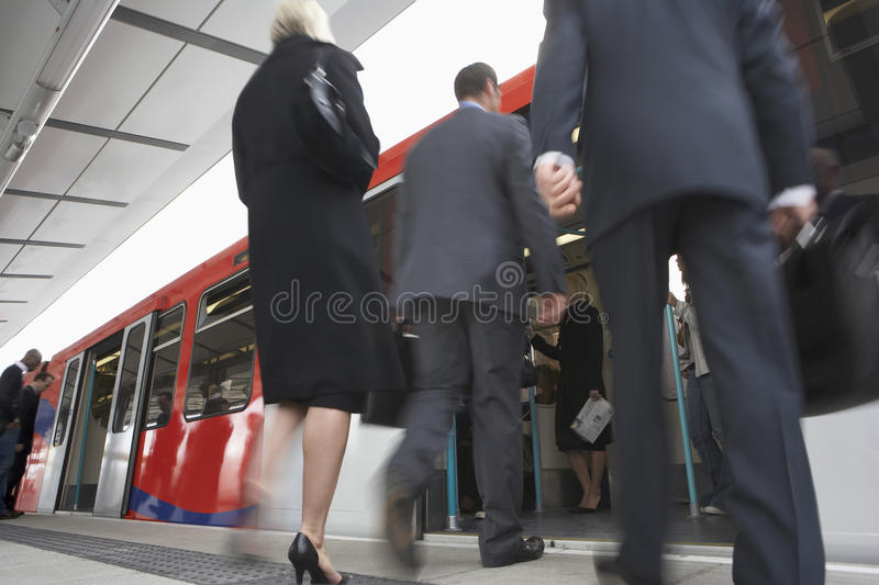 Business Commuters Getting Into Train. Low angle view of business commuters getting into a train royalty free stock image
