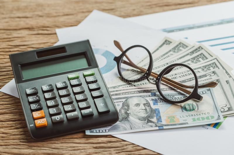 Business or company profit and loss calculation concept, eyeglasses put on pile of US dollar bills and performance revenue. Summary by year and quarter report stock images