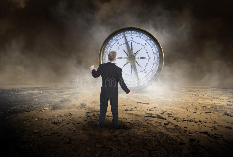 Business Compass, Sales, Goals, Marketing. Abstract concept for business, sales, goals, success, and marketing. A businessman stands in a desolate desert and is stock photography