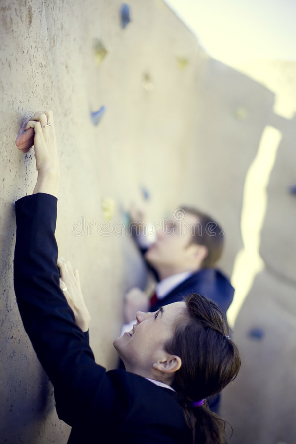 Business competition. Businessman and businesswoman climbing to the top of the wall stock photography