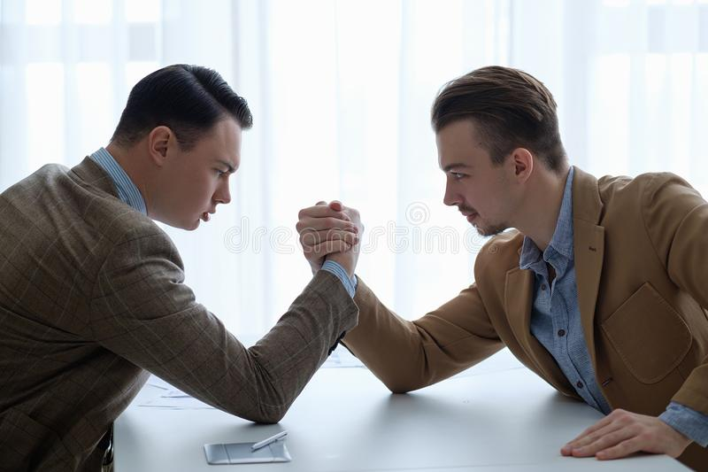 Business competition arm wrestling focused men hands stock photo