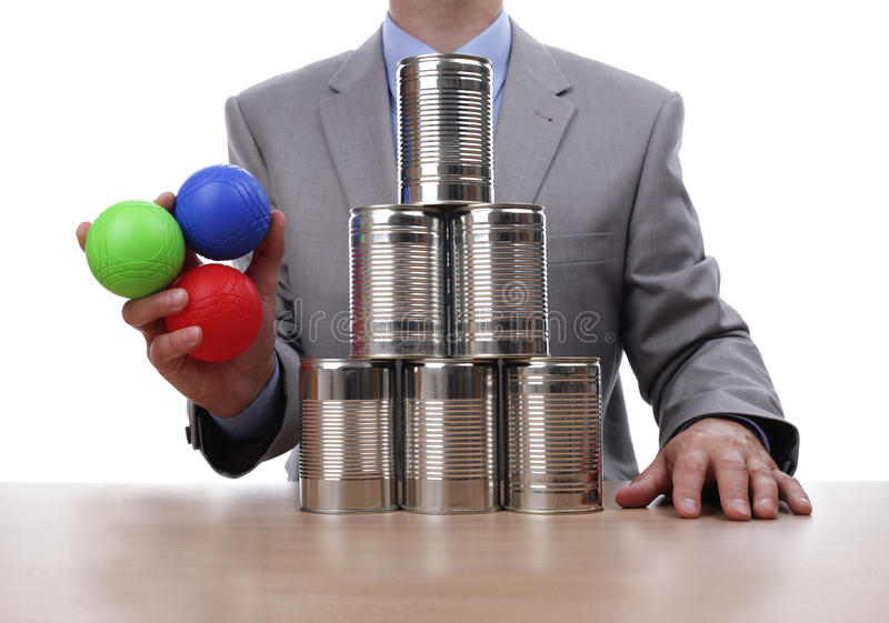 Business competition. Businessman holding balls for tin can alley style business challenge concept for competition, chance, fortune or opportunity royalty free stock photos